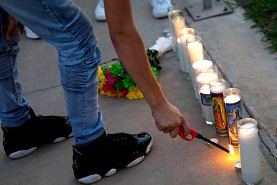 A person attending a vigil for Leilah Hernandez, one of the victims of the Texas shootings in Odessa and Midland, lights a candle on Sept. 2, 2019.