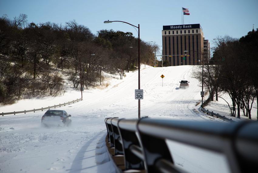 Vehicles attempt to drive uphill through snow and ice on West 15th St. in Austin on Feb. 15, 2021.