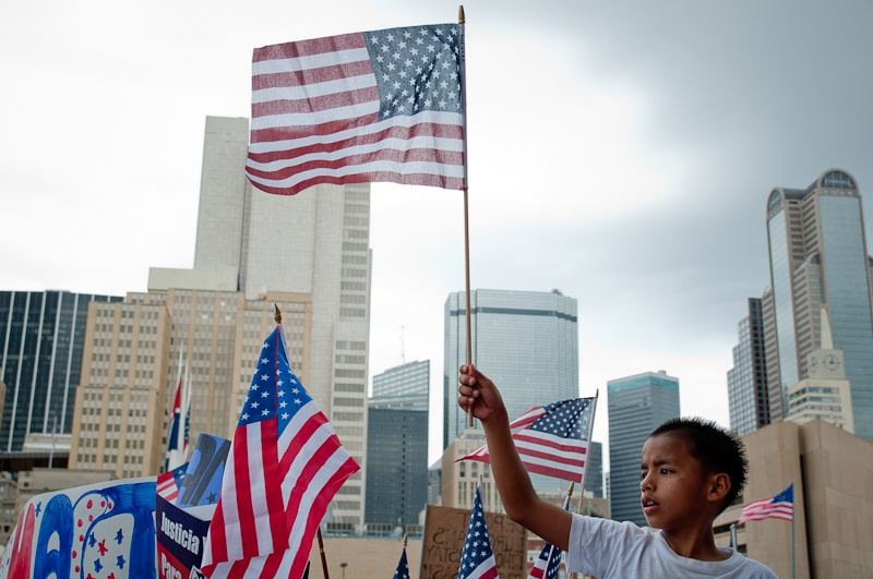 A boy waves an American flag at an immigration rally held in Dallas on May Day.