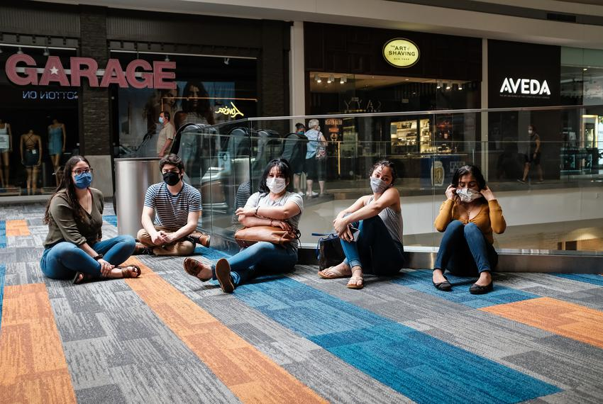 A group of friends sit on the floor and chat at the Barton Creek Square Mall on its first day open after being closed beca...