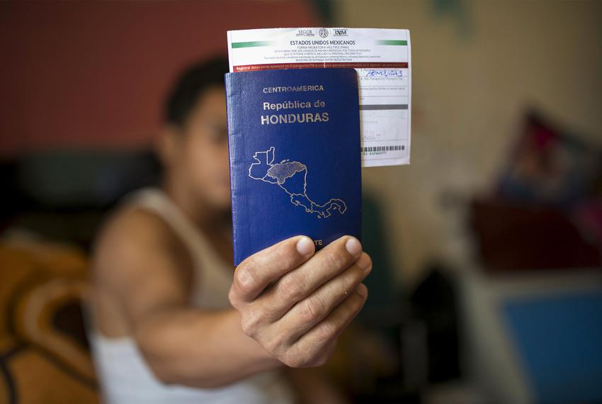 "A young man from Honduras who goes by ""Alexander"" holds his passport and Mexican documents in his room at the house he has b…"