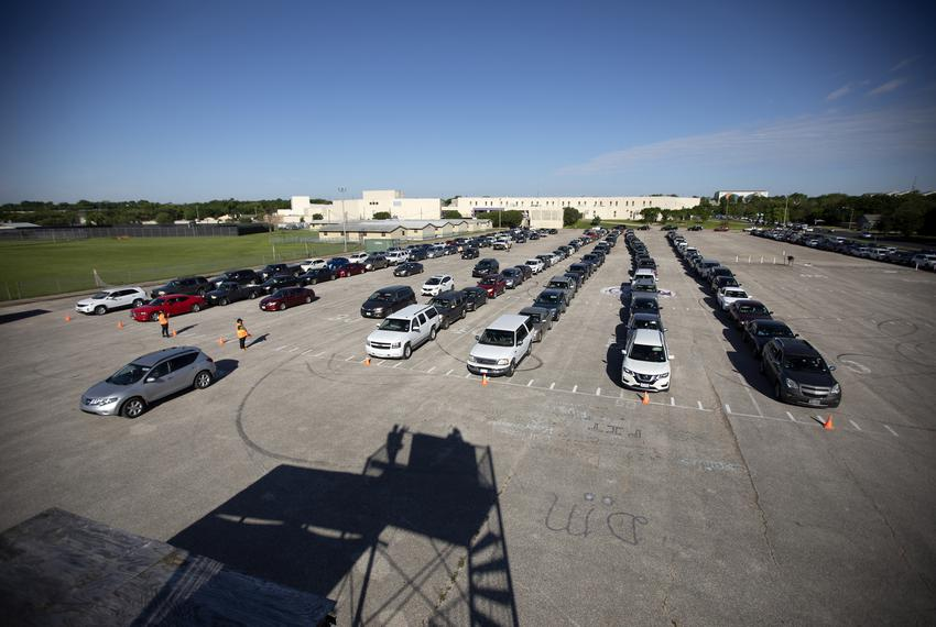 Cars line up at LBJ Early College High School in Austin to receive food and hygiene products from the Central Texas Food B...