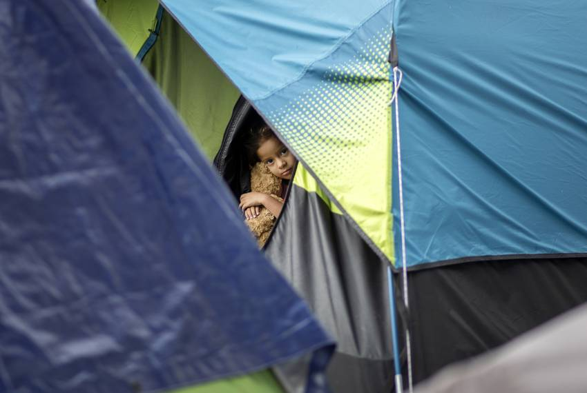 A young girl looks out of a tent at the migrant camp in Matamoros, Tamaulipas. Oct. 17, 2019.
