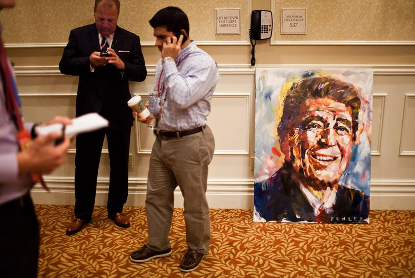 A painting of Ronald Reagan sits off to the side as New Jersey Gov. Chris Christie speaks to the Michigan delegation at the …