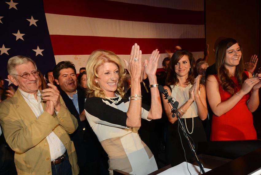 Wendy Davis, flanked by her father, Jerry Russell at left and her two daughters, at right, applauds her supporters during he…