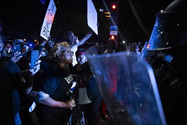 Protesters confront a line of Dallas police officers during the march in Dallas.