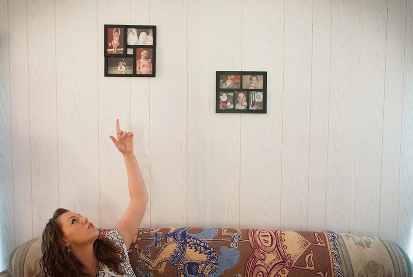 Megan Winfrey, 25, points at photos of her daughter Danielle Hammond, 7, in her mobile home in Coldspring, Texas, Thursday, …