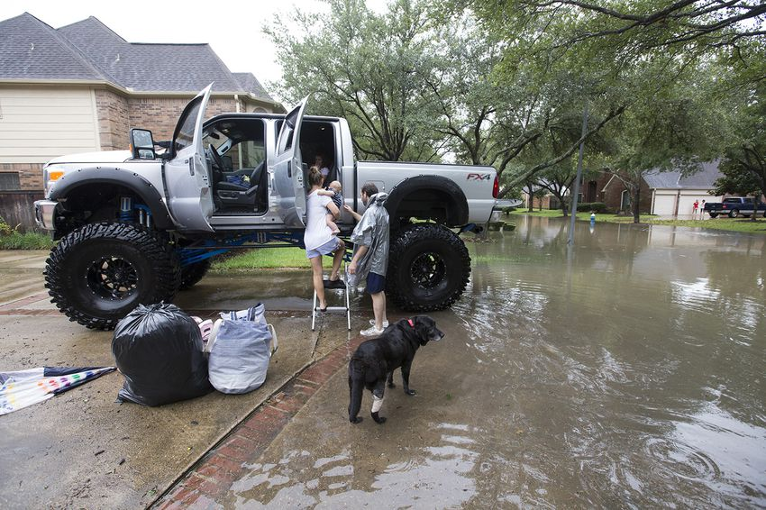 Chris Ginter, right, helps a family into his truck in Houston on Tuesday, Aug. 29, 2017. Ginter is helping evacuate people from their flooded neighborhood near Buffalo Bayou.