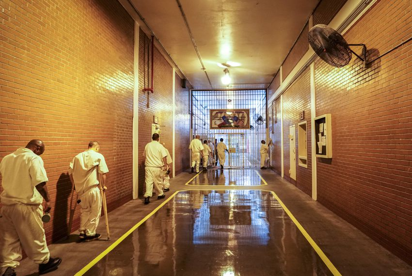 Inmates shuffle past fans in the Darrington prison's main hallway on a hot July day.