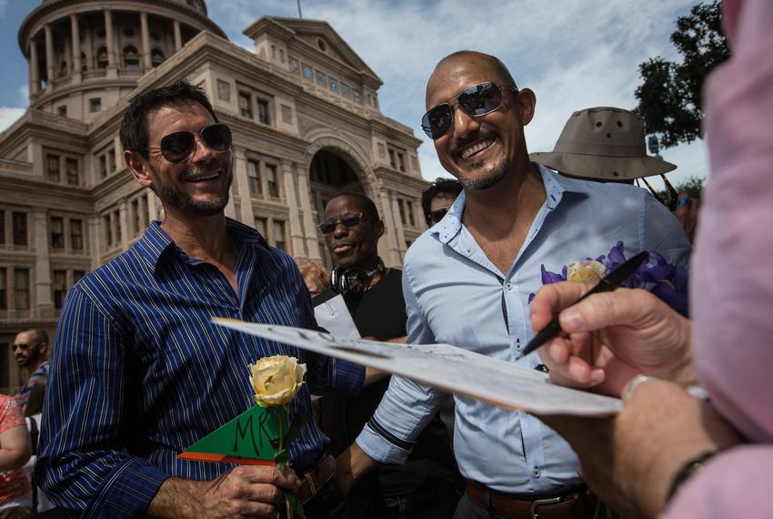 "Herbert Clayson Cloete and Mark Chavez smile as they watch Jodie Flint, who officiated the ""Big Gay Wedding"" ceremony, sign …"