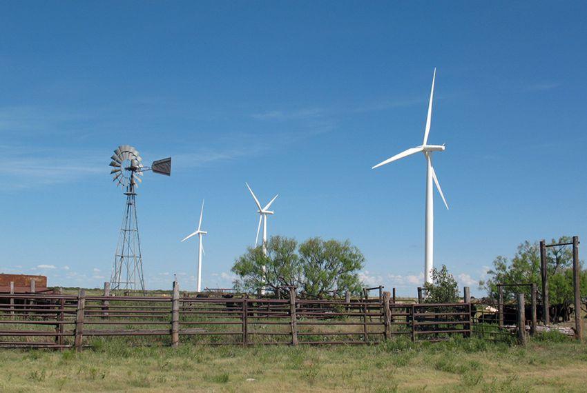 New turbines tower over an old windmill at the Whirlwind wind farm, near Floydada