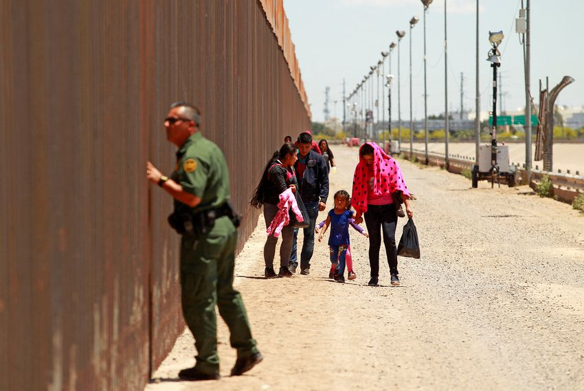 A group of  migrants walks next to the U.S.-Mexico border fence after crossing the borderline while a Border Patrol agent looks through the fence in El Paso on May 15, 2019.
