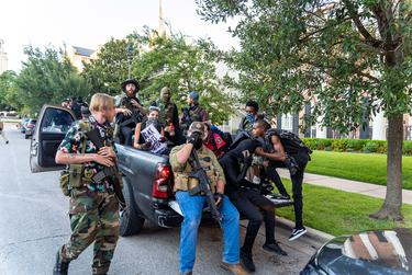 Armed protest sympathizers ride in the back of a pickup truck from a rally on the University of Texas campus to a memorial for Garrett Foster in downtown Austin, minutes after hearing of clashes between protesters and police.
