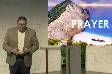 Preaching Minister David Duncan says prayer during a livestreamed service in Houston.