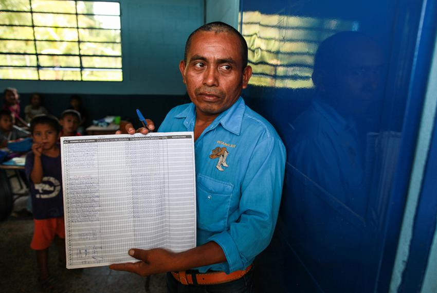 """Carlos Pop, Byron's first-grade teacher in San Miguel Limón, shows his class roster. """"In my class, I have 19 students,"""" said…"""