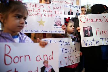 Children hold up signs while waiting in line to enter the rally for Donald Trump in Fort Worth on Feb. 26, 2016.