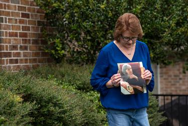 Genny Lutzel holds a photograph of her mother, Paula Spangler, 80, outside her home in Rockwall on Aug. 06, 2020. Lutzel hasn't seen her mother, who lives in a nursing home and suffers from Alzheimer's, since March due to COVID-19.