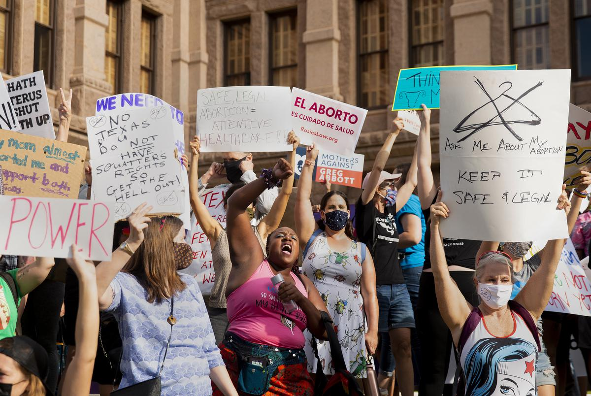 Pro-choice attendees chant and stand to block a small pro-life counterprotest from view during the Womenís March ATX at the Texas Capitol in Austin, Texas, on Saturday, Oct. 2, 2021. Thousands of people attended the rally in support of womenís reproductive health and access to safe abortions.