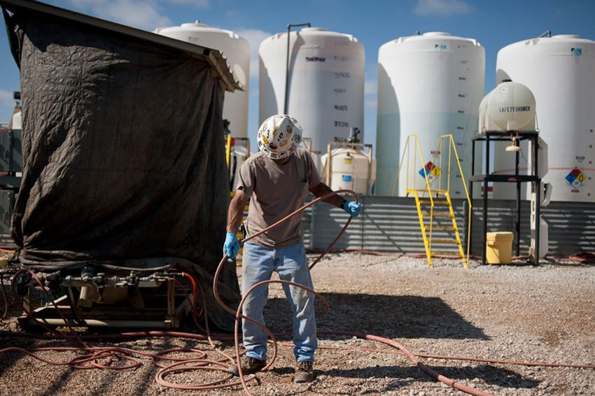 A worker untangles a hose at a Fountain Quail water management and treatment facility in Roanoake, Texas. Fountain Quail cleans and separates water used in fracking for natural gas removal.