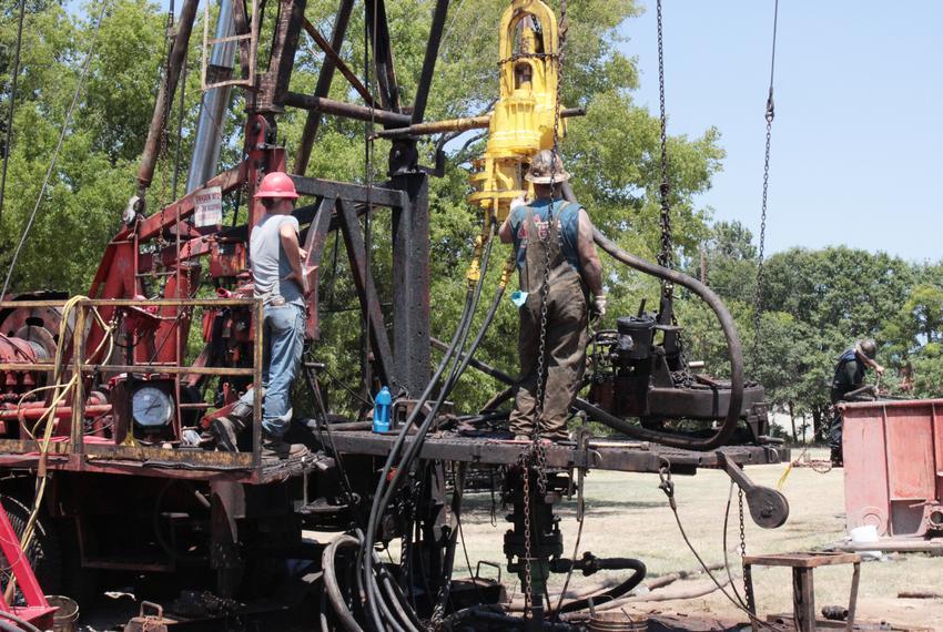 Roughnecks repair a leaking oil well near downtown Kilgore.