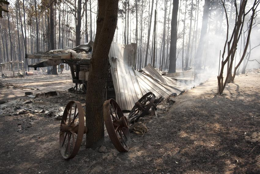 The remains of a mobile home lie smoldering in a small subvision east of Bastrop where the wildfire went through earlier i...