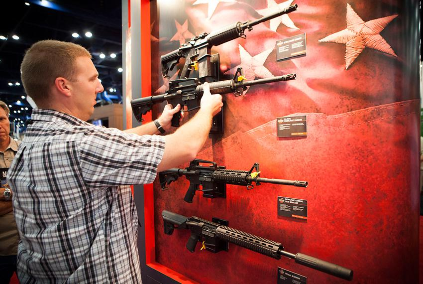 A man who declined to be identified looks at Bushmaster rifles at the NRA's national convention in Houston, Friday May 3, 20…