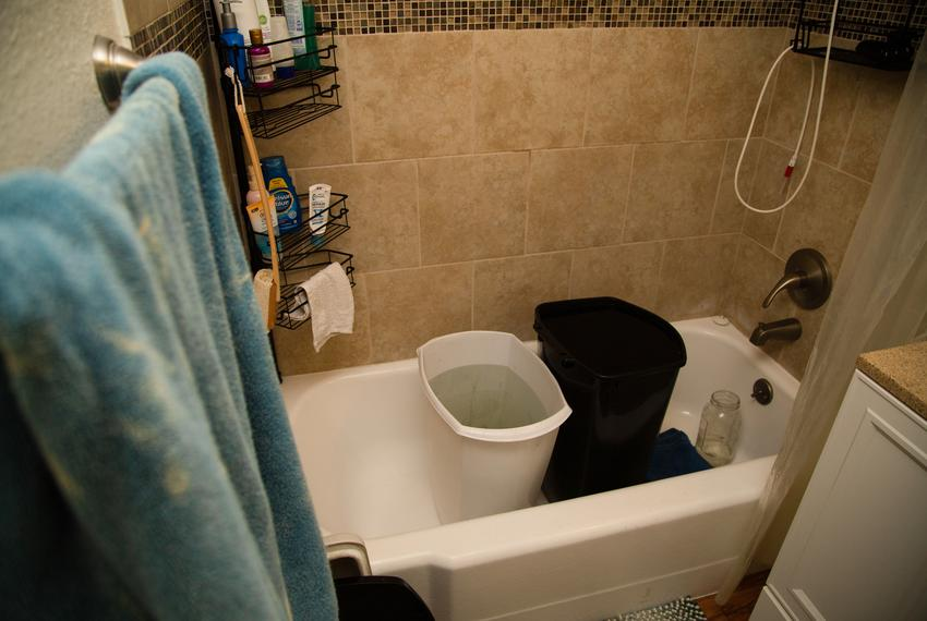 Two trashcans full of water sit inside a bathtub in Whitaker Brand's apartment in Austin on Feb. 24, 2021.