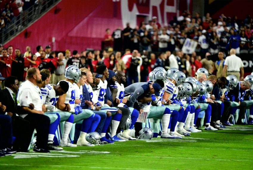 The Dallas Cowboys football team takes a knee prior to the national anthem during a game against the Arizona Cardinals on Sept. 25, 2017.