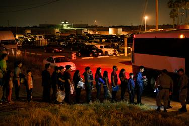 Migrant families who turned themselves in to U.S. Border Patrol to seek asylum after illegally crossing the Rio Grande are loaded onto a transport bus in Hidalgo on Aug. 23, 2019.