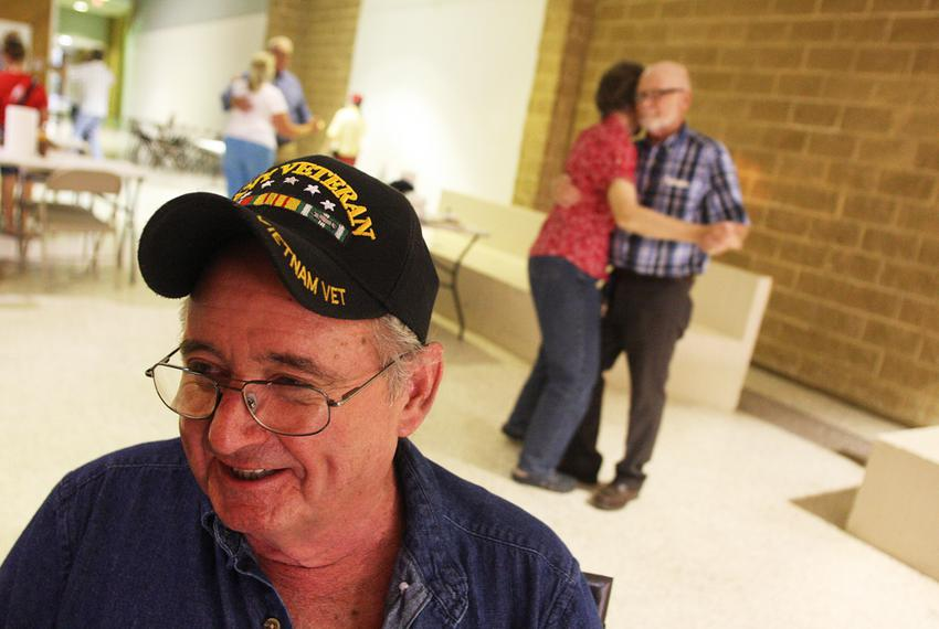 David Rockwell, 64, a Navy Vet who served in the Vietnam War, laughs with friends while other participants in the family nig…