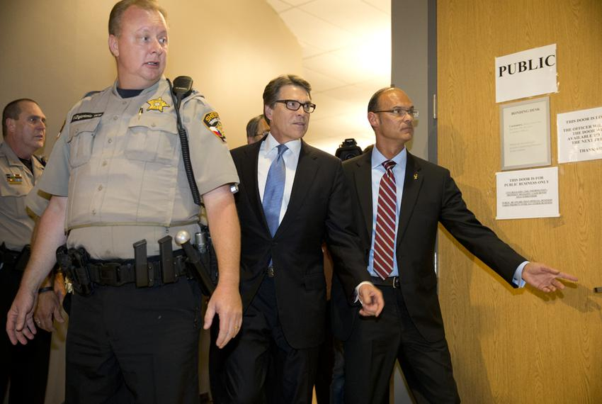 Governor Rick Perry is led into the booking area of the Travis County Courthouse for fingerprints and photographs on August …