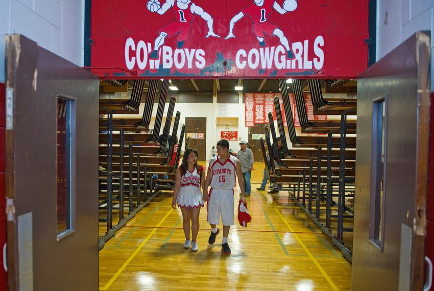 Premont High School cheerleader Stacy Morales, 17, and student basketball player Ernesto Gonzalez leave the gym after a ga...