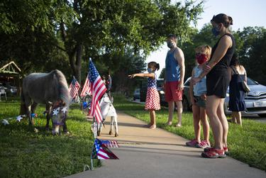 Families interact with a miniature horse at a decorated house as part of Allandale Neighborhoodís Reverse Parade for the Fourth of July on Saturday, July 4, 2020 in Austin. The neighborhood decorated houses and invited neighbors to walk, bike or drive by to celebrate the holiday at a social distance.