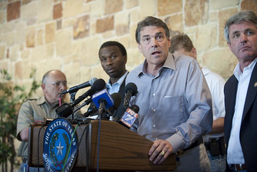 A tired-looking Gov. Rick Perry listens to a reporter's question at the Bastrop Civic Center during a press conference on th…