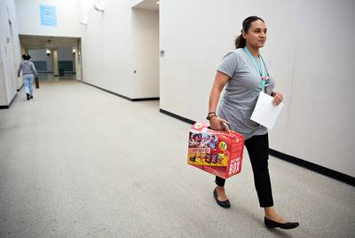 Tiffany Robinson, a science instructional specialist, carries a box of snacks to entice students to stay for an after-school tutorial on April 19, 2018.