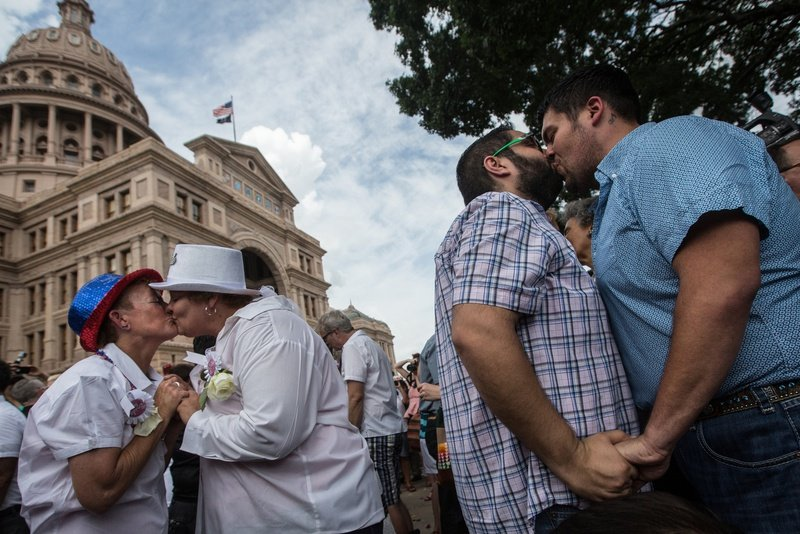 """Couples embrace at the conclusion of the """"Big Gay Wedding"""" ceremony on the south lawn of the Texas Capitol on July 4 after the Supreme Court legalized same-sex marriage in June."""