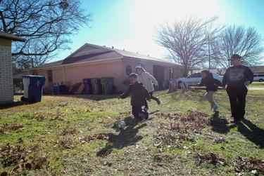 Frances Sanchez plays soccer with her three children, Pedro Sanchez (left), 9, Katrina Sanchez, 12 almost 13, and Samaria Sanchez, 9 in the front yard of a friends house where they are staying. It has been a rough year for Sanchez, losing custody of her kids and becoming homeless started an exhausting cycle of living paycheck to paycheck.