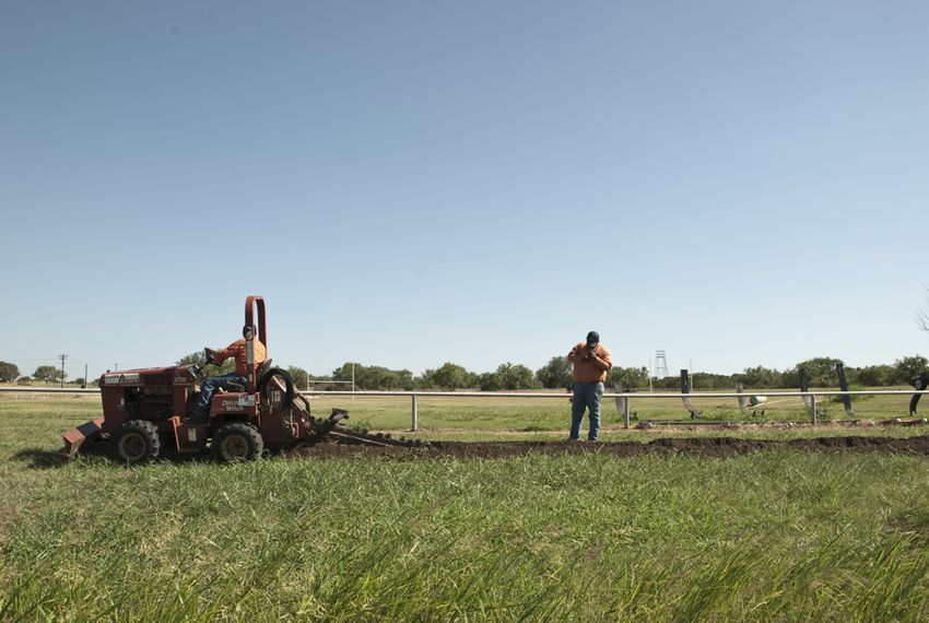 Outdoor watering has been banned in Llano, so workers dug a ditch in late June before laying a pipe that will bring well water to football practice fields.