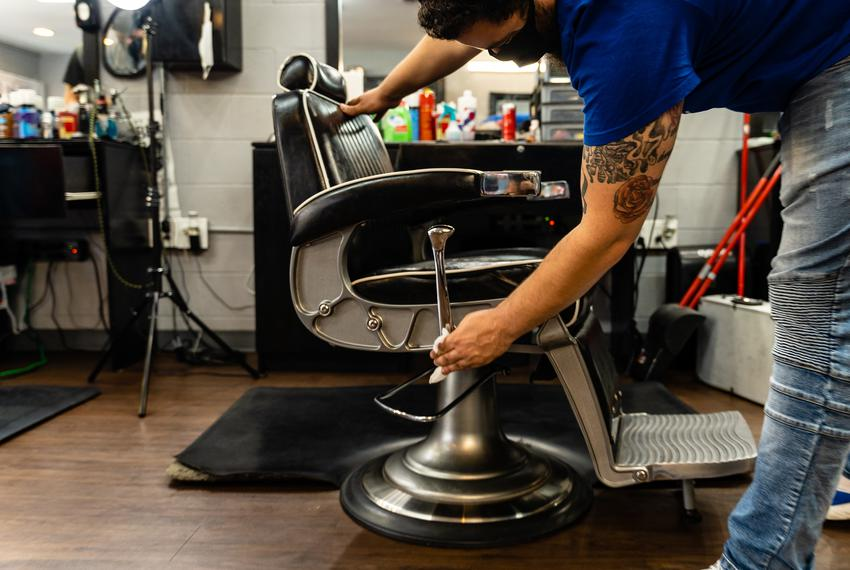 Demeatric Callaway, a barber at Kane's Barbershop in East Austin, wipes down his chair with disinfectant in preparation fo...