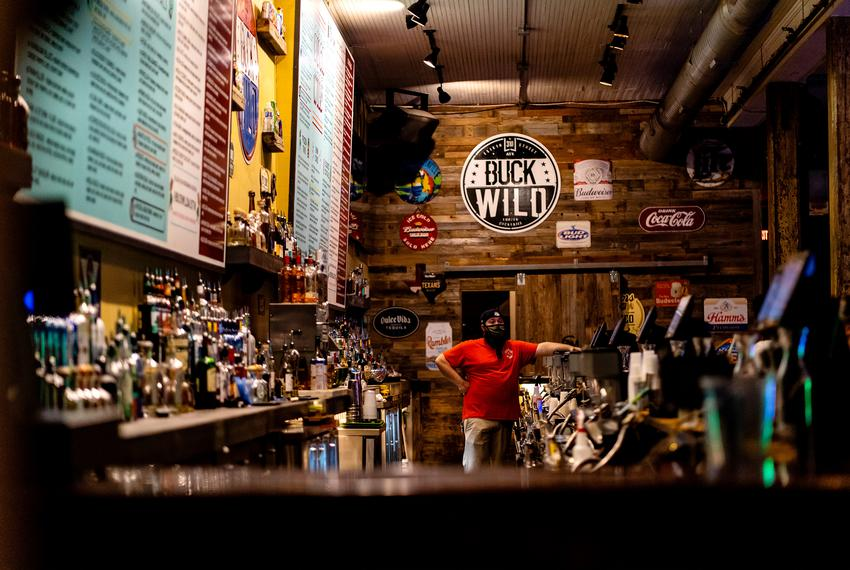 A bartender waits for customers at Buck Wild on West 6th street in downtown Austin as bars reopen on May 22, 2020.