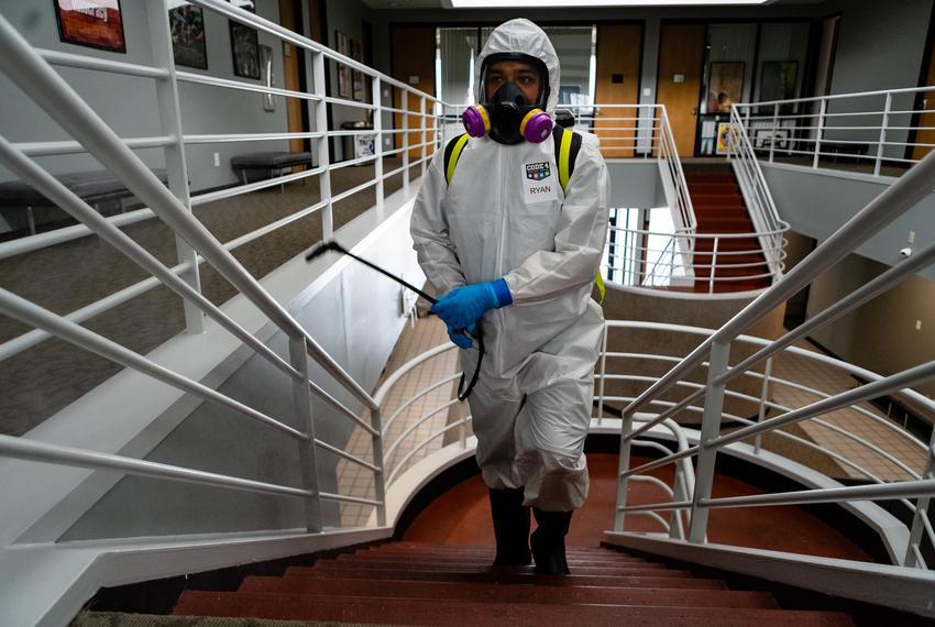 A worker for Code 4 Event Management sprays disinfectant on a staircase as he and his colleagues disinfect a building duri...