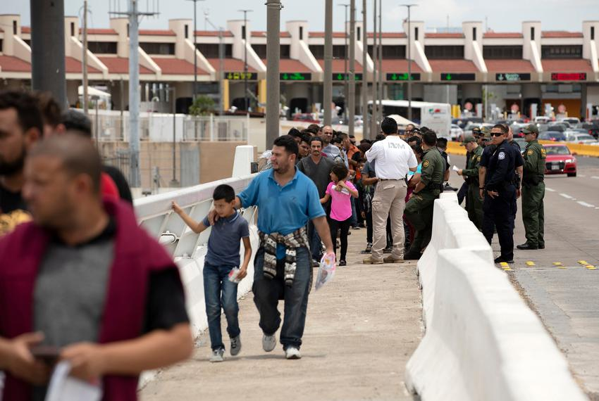 A group of migrants walk across Internation Bridge Two into Mexico from the United States. The group requested asylum in the…