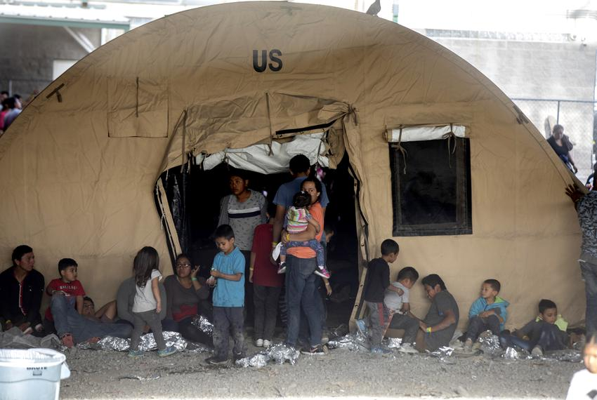 Families outside a tent at a temporary migrant holding area set up by Customs and Border Protection under the Paso del Nor...