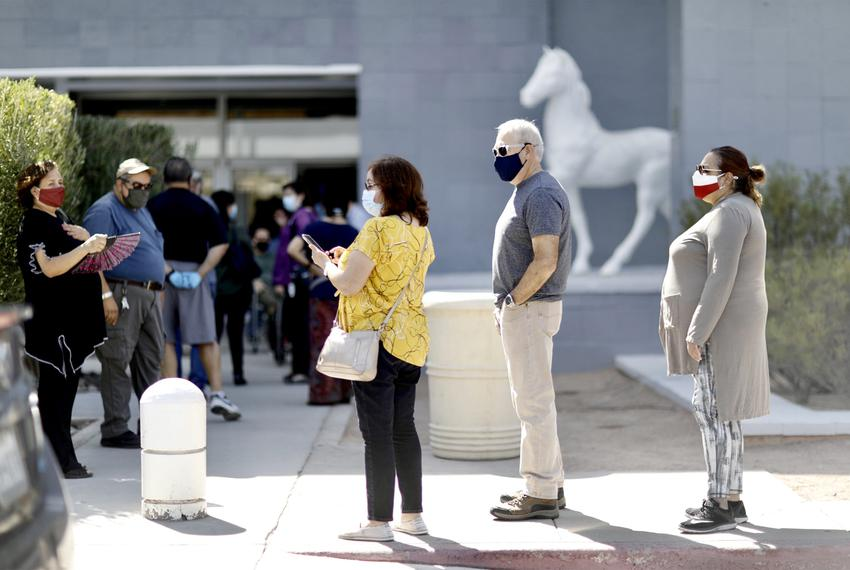 Voters wait in line to cast their ballots at the Sunland Park Mall in El Paso on the first day of early voting in Texas on O…