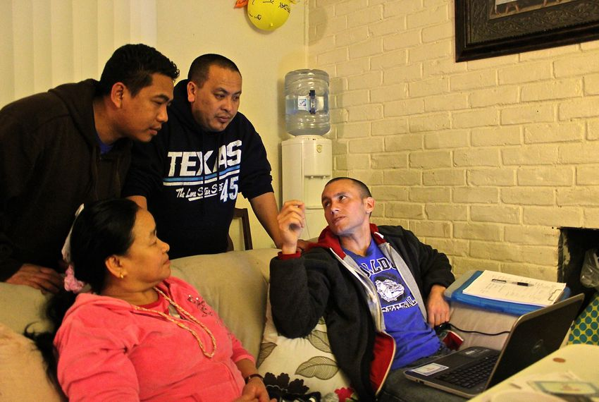 Eddie Almodovar, far right, a volunteer, helped refugee Aruna Rai, seated, sign up for a health insurance plan at an Austin apartment on Jan 30, 2014. Fellow refugees Khamba Magar, top left, and John Monger served as interpreters.