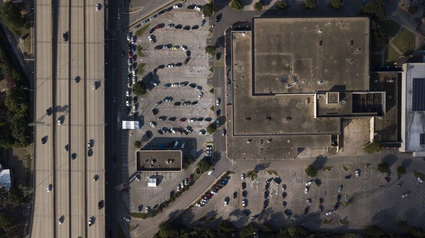 Starting from the bottom right corner, a line of cars snakes through the parking lot at Hancock Center in Austin while waiti…
