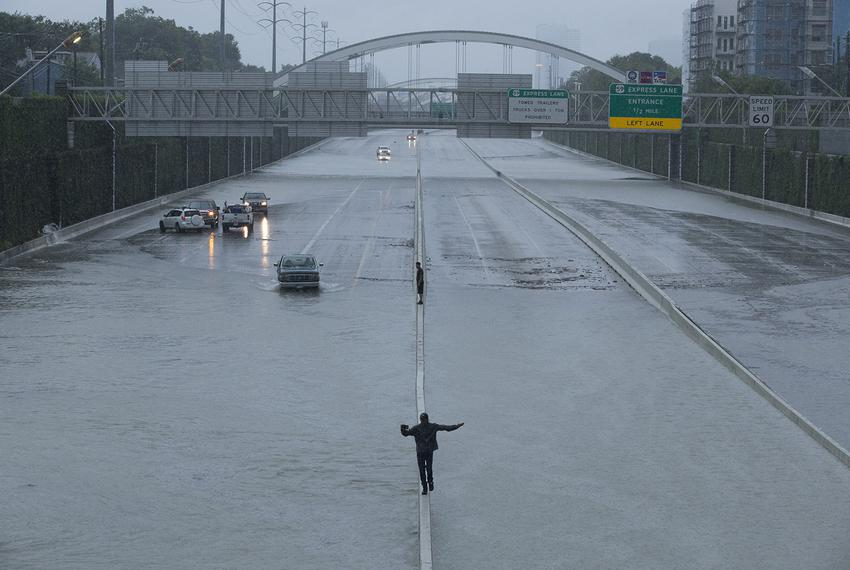 People balance on the Southwest Freeway divider in Houston as cars turn away from flooding on Sunday morning, Aug. 27, 2017.