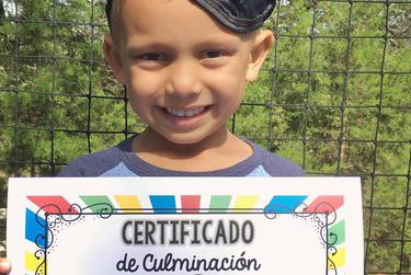 Nikhil Shah, 5, shows off his certificate for completing pre-K.