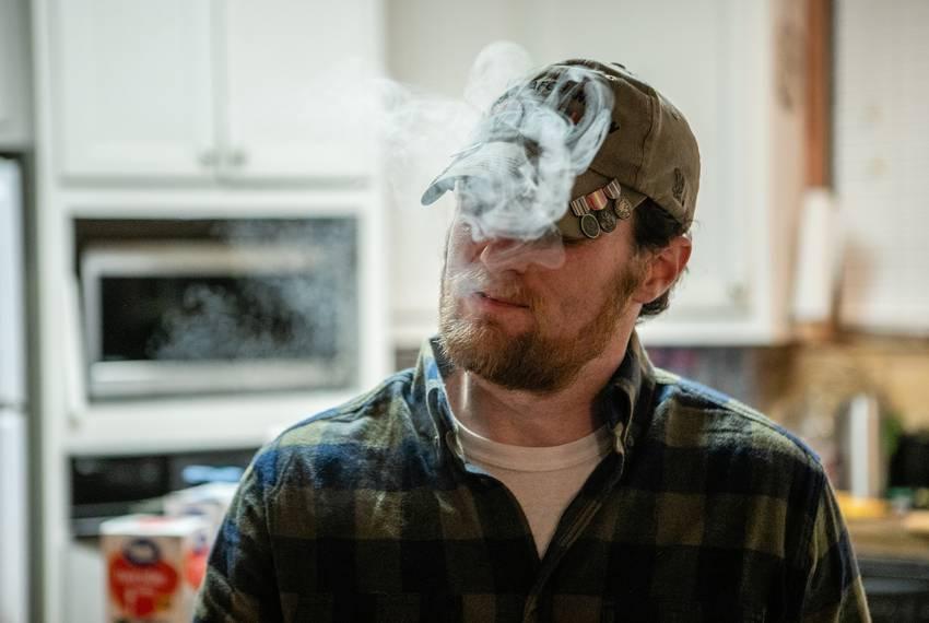Joshua Raines, an Afghanistan combat veteran and Purple Heart recipient, smokes from his marijuana vape pen after returnin...