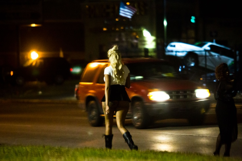 """Women """"walk the track"""" on a stretch of Bissonnet Street in Houston. Pimps gather nearby in fast food and strip mall parking lots as potential johns circle and standard traffic passes through."""